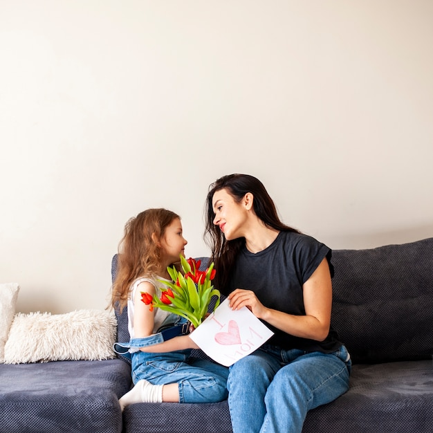 Adorável jovem dando flores para sua mãe