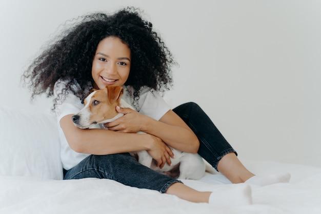 Adorável jovem dono do animal feminino poses no quarto branco limpo, abraça o cão