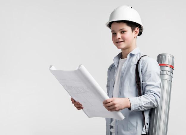 Adorável jovem engenheiro segurando o plano de construção