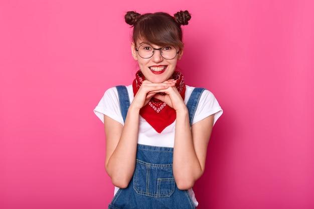 Adorável jovem estudante encantadora, tocando seu queixo com as duas mãos, olhando diretamente para a câmera, sendo alegre, vestindo óculos elegantes redondos, macacão jeans, bandana vermelha e camiseta branca.