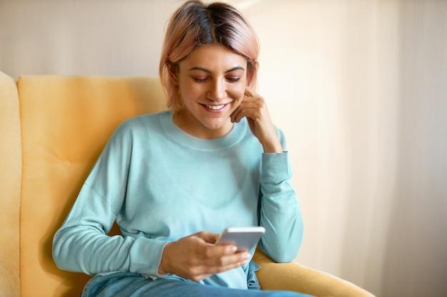 Adorável jovem europeia com argola no nariz e cabelo rosado, sentada na poltrona com o celular, enviando mensagens de texto para amigos, desfrutando da comunicação online.