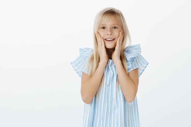 Adorável jovem europeia com cabelo loiro em uma blusa azul da moda, ofegante, de mãos dadas perto da boca aberta, sorrindo amplamente enquanto se surpreende e se surpreende, admirando o filhote de cachorro fofo sobre a parede cinza