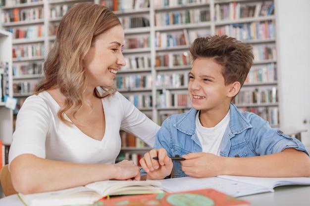 Adorável jovem falando com seu lindo filho pequeno enquanto fazia tarefas escolares na biblioteca