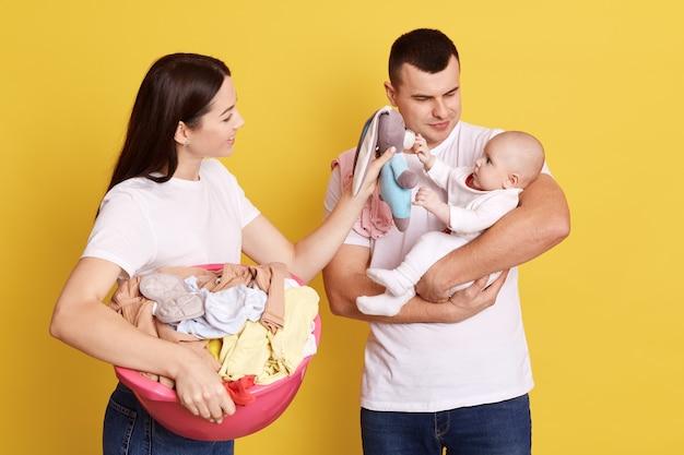 Adorável jovem família de três sendo fotografada contra a parede amarela, mamãe fazendo landry e segurando a bacia cheia de roupas sujas, pai com criança nas mãos tentando confortar o bebê, mamãe mostra o brinquedo.