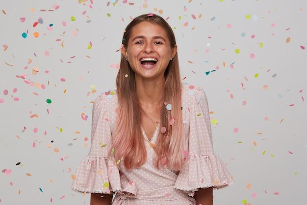 Adorável jovem feliz de cabelos compridos rindo alegremente durante a festa de aniversário com seus amigos, em pé sobre uma parede branca em confetes multicoloridos