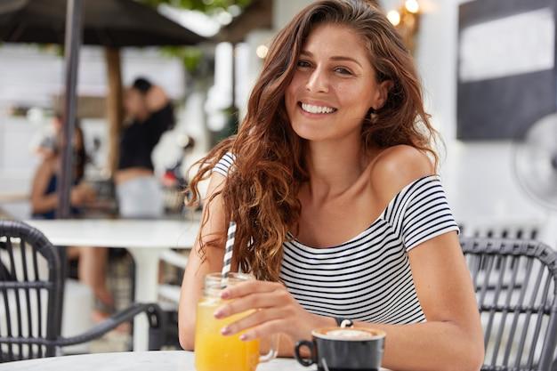 Adorável jovem fêmea com cabelo comprido escuro, vestida com uma camiseta listrada na cafeteria, bebe suco fresco e café expresso.
