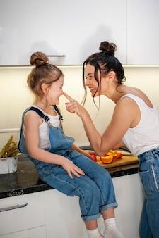 Adorável jovem garota e mãe junto na cozinha