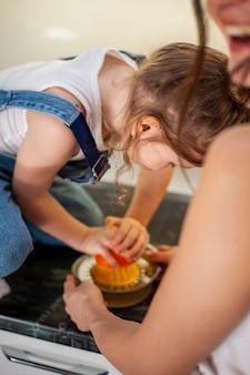 Adorável jovem garota e mãe preparando suco de laranja