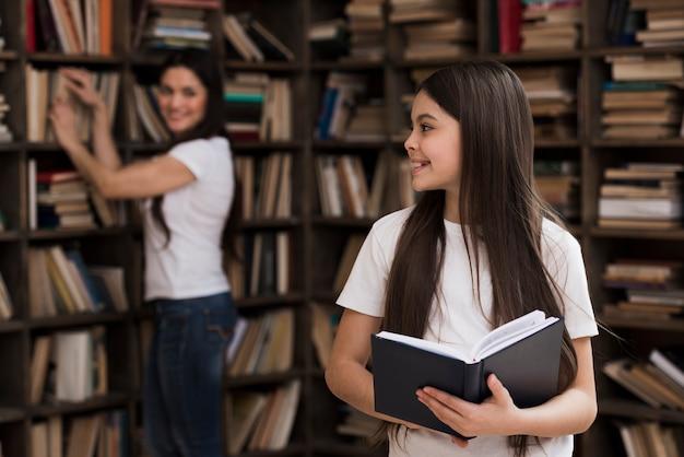 Adorável jovem garota e mulher na biblioteca