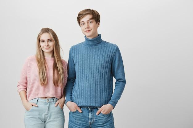 Adorável jovem garoto e garota caucasiana vestindo jeans e blusas de malha