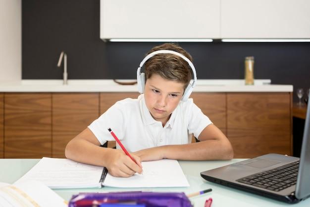 Adorável jovem garoto fazendo sua lição de casa