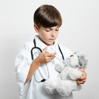Adorável jovem garoto segurando um ursinho de pelúcia