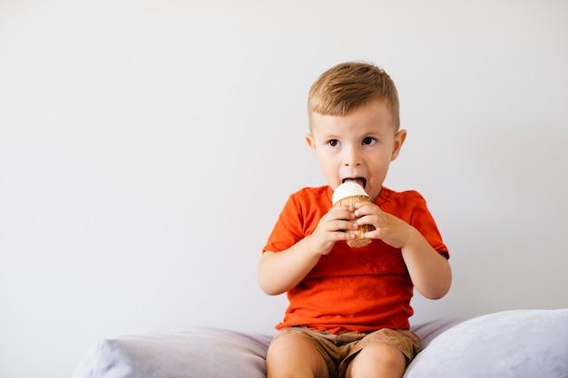 Adorável jovem garoto tomando sorvete