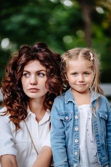 Adorável jovem mãe e filha em um dia ensolarado, família feliz