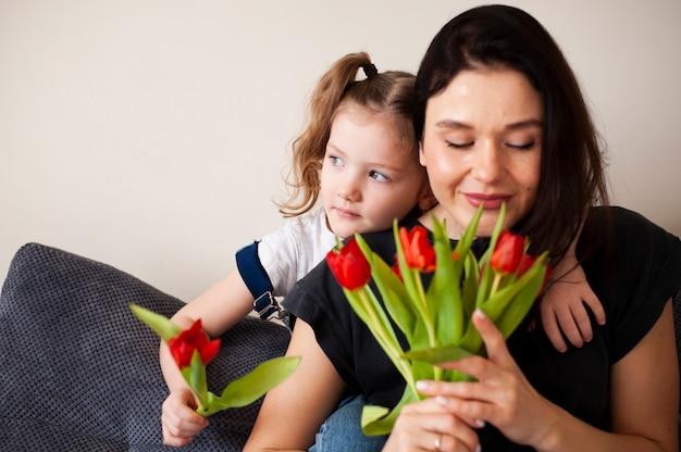 Adorável jovem mãe surpreendente com flores