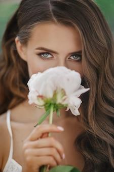 Adorável jovem mantém flor branca antes de seu rosto