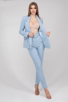 Adorável jovem moda feminina modelo posando de terninho azul na moda comprimento total isolado