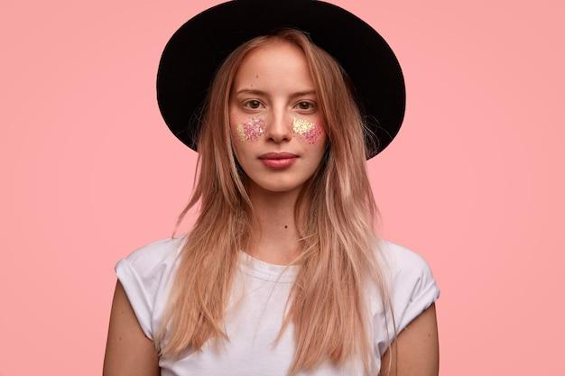 Adorável jovem modelo europeu com glitter no rosto, usa elegante chapéu preto, camiseta branca, posa sobre uma parede rosa, pronta para o festival com os amigos