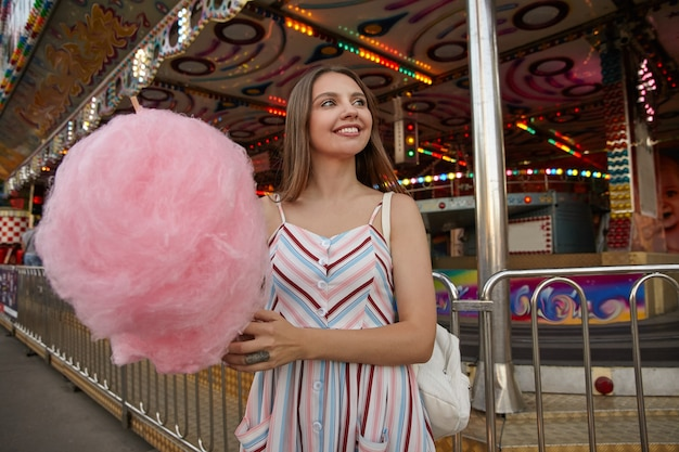 Adorável jovem morena olhando para o lado com um sorriso encantador, usando um vestido romântico e uma mochila branca, caminhando pelo parque de diversões com algodão doce na vara
