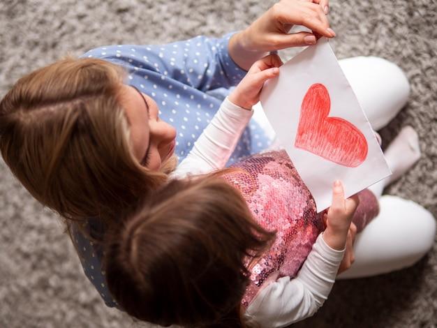 Adorável jovem mostrando o desenho para a mãe dela