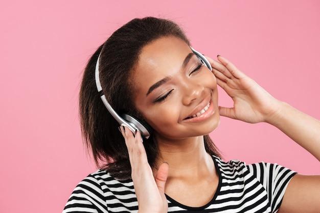 Adorável jovem mulher africana gosta de ouvir música em fones de ouvido