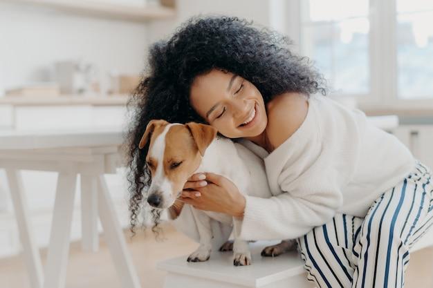 Adorável jovem mulher afro-americana encaracolada abraça o amado cão de raça com amor, tem um sorriso gentil