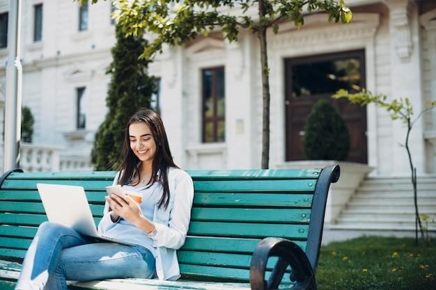Adorável jovem mulher com longos cabelos escuros, olhando para seu smartphone, sorrindo enquanto segura uma xícara de café com um laptop nas pernas contra um edifício.