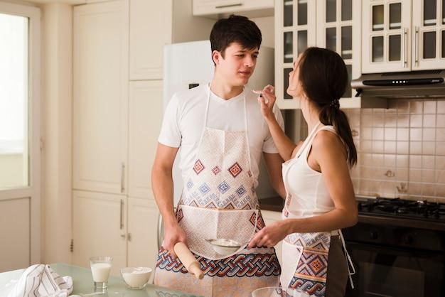Adorável jovem mulher e homem junto na cozinha