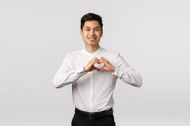 Adorável jovem namorado asiático em camisa formal, calça, mostrando sinal de coração expressar amor, carinho ou admiração, sorrindo câmera, convidar namorada ir baile juntos, em pé