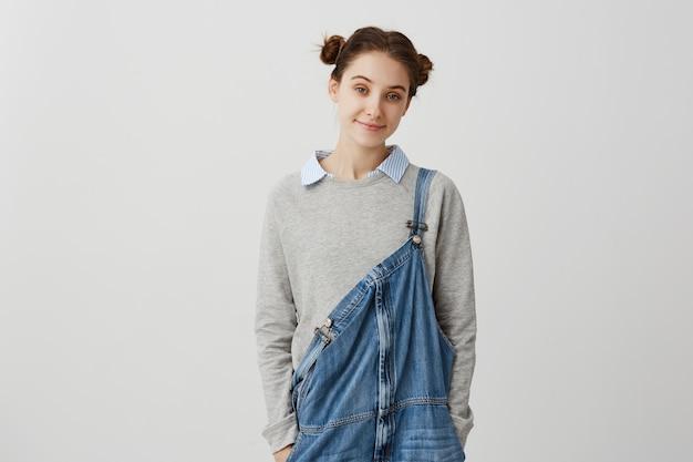 Adorável jovem procurando em macacão jeans casual. afável senhora morena com cabelos em pães duplos, aproveitando o tempo ficando em casa no fim de semana. conceito de aconchego