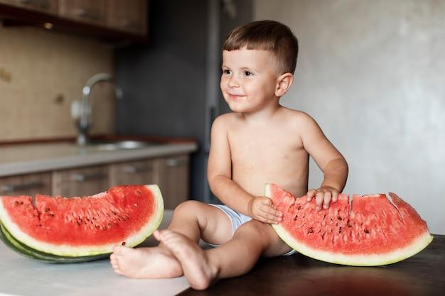 Adorável jovem rapaz com fatias de melancia