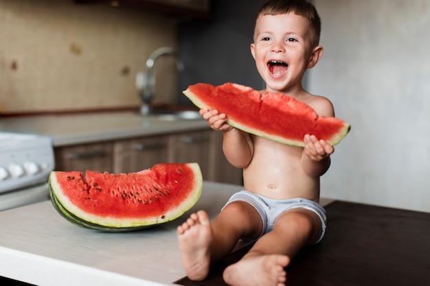 Adorável jovem rapaz comendo melancia