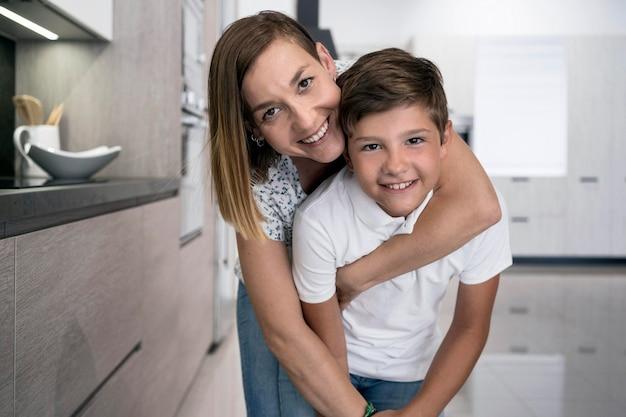 Adorável jovem rapaz posando com a mãe