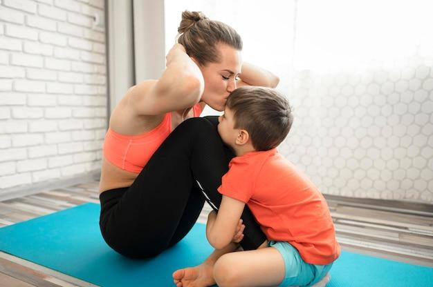 Adorável jovem rapaz treinando com a mãe