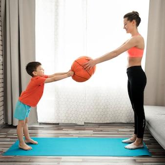 Adorável jovem rapaz treinando com sua mãe