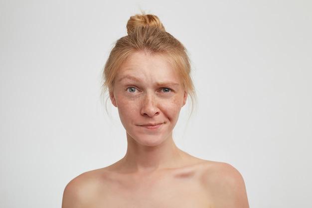 Adorável jovem ruiva com penteado coque levantando a sobrancelha enquanto e contorcendo a boca, em pé sobre uma parede branca