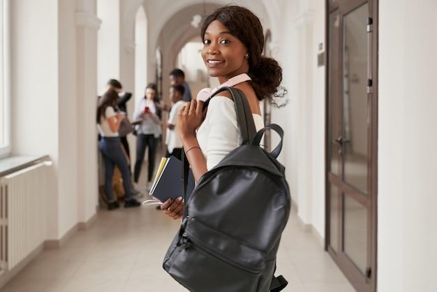 Adorável jovem sorridente negra está olhando para a câmera em meia volta e mantendo a mochila preta no ombro e o caderno cinza na mão direita.