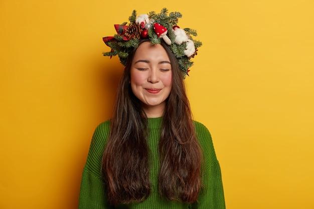 Adorável jovem sorrindo agradavelmente usando coroa de flores festiva na cabeça