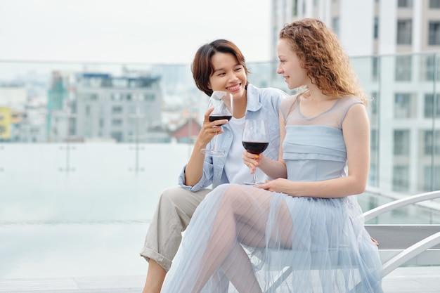 Adorável jovem vietnamita apaixonada bebendo um copo de vinho tinto e olhando para sua namorada sorridente