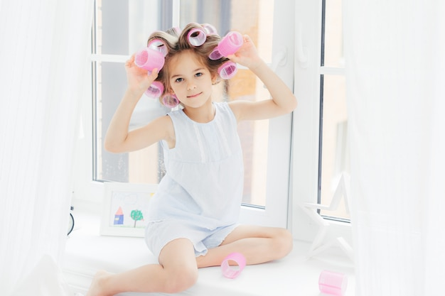 Adorável linda garota com rolinhos no cabelo, senta-se no peitoril da janela em casa, vai ter um penteado encaracolado
