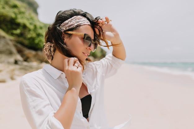 Adorável linda mulher com cabelos escuros ondulados, vestida de camisa branca e óculos de sol pretos se diverte na praia branca perto do oceano com um sorriso adorável.