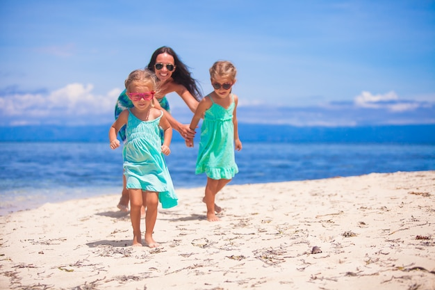 Adorável little girls e jovem mãe se divertir na praia tropical branca na ilha deserta