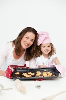 Adorável mãe e filha mostrando um prato com biscoitos