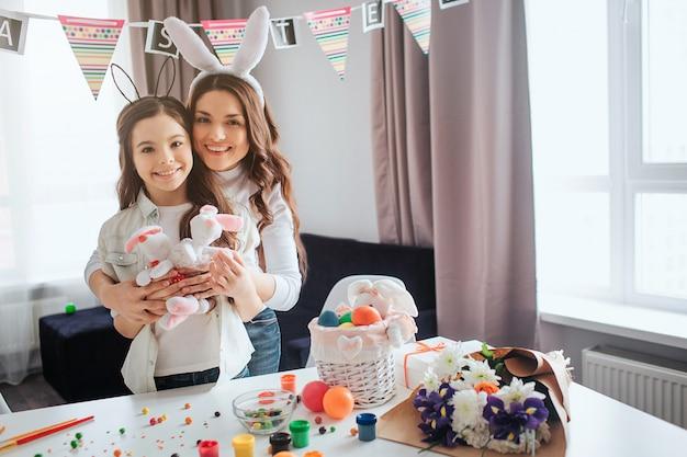 Adorável mãe e filha positivas se preparam para ester. eles seguram brinquedos de coelho e sorriem para a câmera. mãe abraço filha. decoração e pintura na mesa na sala.