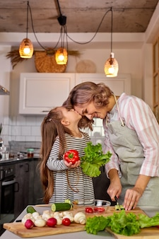 Adorável mãe e filha se beijando na cozinha enquanto cozinham, preparando salada fresca de vegetais