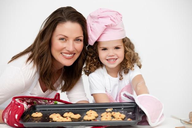 Adorável mãe e filha segurando um prato com biscoitos