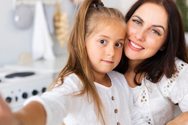 Adorável mãe e filha tomando selfies