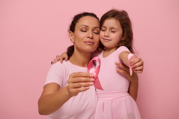 Adorável mãe mestiça abraça uma menina em trajes rosa e exibe uma fita de cetim rosa para a câmera, símbolo do dia do câncer de mama no mês de outubro. suporte para pacientes com câncer e sobreviventes