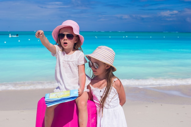Adorável menina à procura de caminho com um mapa e grande mala na praia