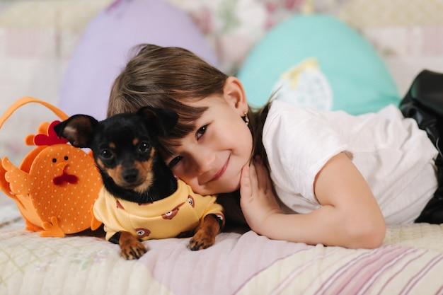 Adorável menina abraça seu animal de estimação em casa no sofá, criança se preparando para a páscoa em casa durante a quarentena